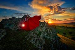 Belle femme avec le manteau rouge dans la lumière de coucher du soleil photographie stock