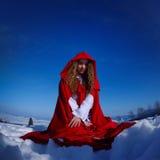 Belle femme avec le manteau rouge se reposant sur la neige Image libre de droits