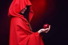 Belle femme avec le manteau rouge tenant la pomme photographie stock