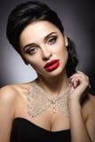 Belle femme avec le maquillage de soirée, les lèvres rouges et la coiffure de soirée Visage de beauté Image stock