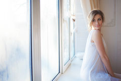 belle femme avec le maquillage quotidien frais et la coiffure onduleuse romantique, se reposant au rebord de fenêtre images stock