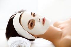 Belle femme avec le masque cosmétique sur le visage. La fille obtient le traitement Images stock