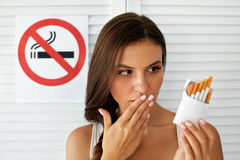 Belle femme avec le paquet des cigarettes et du signe non-fumeurs Photos stock