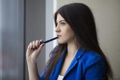 Belle femme avec le stylo près de la fenêtre photos stock