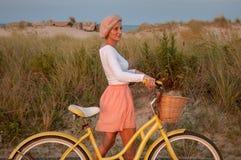 Belle femme avec le vélo sur la plage photo stock