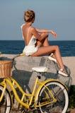 Belle femme avec le vélo sur la plage image libre de droits