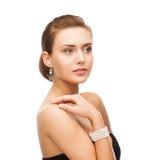 Belle femme avec les boucles d'oreille et le bracelet de perle Image stock