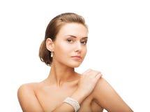 Belle femme avec les boucles d'oreille et le bracelet de perle Photo stock