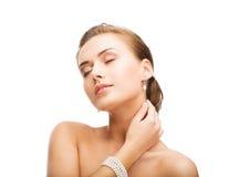 Belle femme avec les boucles d'oreille et le bracelet de perle Images stock