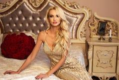 Belle femme avec les cheveux blonds dans des vêtements luxueux posant avec image stock