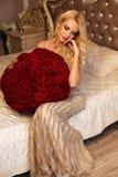 Belle femme avec les cheveux blonds dans des vêtements luxueux posant avec images stock