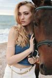 Belle femme avec les cheveux blonds posant avec le cheval noir Image libre de droits