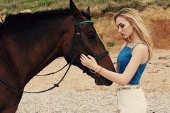Belle femme avec les cheveux blonds posant avec le cheval noir Photos stock