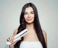 Belle femme avec les cheveux droits et les cheveux bouclés utilisant le redresseur de cheveux Fille mignonne redressant les cheve photos libres de droits