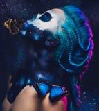 Belle femme avec les cheveux et le papillon bleus images stock