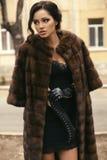 Belle femme avec les cheveux foncés dans le manteau de fourrure et les gants luxueux photographie stock libre de droits