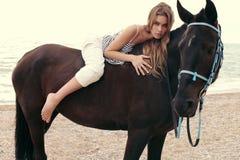 Belle femme avec les cheveux foncés posant avec le cheval noir Photos stock