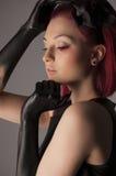 Belle femme avec les cheveux rouges et la peinture noire sur des mains Photos libres de droits