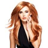 Belle femme avec les cheveux rouges longtemps droits dans une robe noire. Photos libres de droits