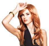 Belle femme avec les cheveux rouges longtemps droits dans une robe noire. Images stock