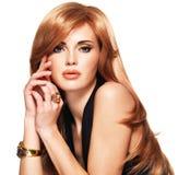 Belle femme avec les cheveux rouges longtemps droits dans une robe noire. Photographie stock libre de droits