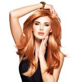 Belle femme avec les cheveux rouges longtemps droits dans une robe noire Photographie stock