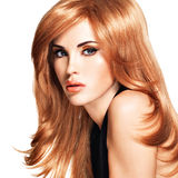 Belle femme avec les cheveux rouges longtemps droits dans une robe noire Photos stock