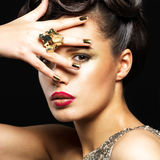 Belle femme avec les clous d'or et le maquillage de style Image libre de droits