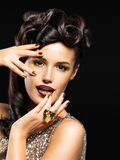 Belle femme avec les clous d'or et le renivellement de mode Photo stock
