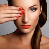 Belle femme avec les clous rouges. Maquillage et manucure. Lèvres rouges Images stock