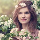 Belle femme avec les fleurs blanches d'Apple Visage mignon photographie stock libre de droits