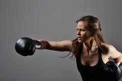 Belle femme avec les gants de boxe noirs photographie stock libre de droits