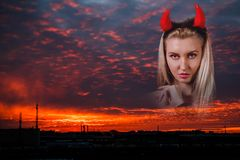 Belle femme avec les klaxons rouges de démon au fond du su Images stock