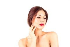 Belle femme avec les lèvres rouges touchant la joue Composez avec les lèvres rouges Photographie stock libre de droits