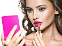 Belle femme avec les lèvres et la fleur rouges lumineuses près du visage Image stock