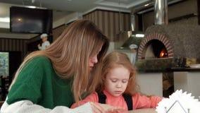 Belle femme avec sa fille observant le menu à un café de pizzeria banque de vidéos