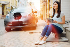 Belle femme avec un comprimé attendant sa voiture Photo libre de droits