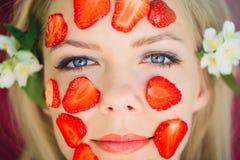 Belle femme avec un masque de fraise, plan rapproché, massage facial, cosmétiques naturels, se trouvant sur la nature dans un jar photos stock