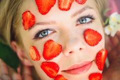 Belle femme avec un masque de fraise, plan rapproché, massage facial, cosmétiques naturels, se trouvant sur la nature dans un jar photo libre de droits