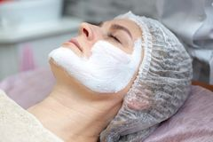 Belle femme avec un masque facial à un salon de beauté photo libre de droits