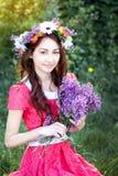Belle femme avec une guirlande et avec un bouquet des lilas image libre de droits