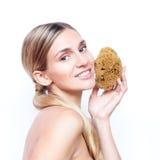 Belle femme avec une peau émouvante d'éponge naturelle et sourire avec des dents photographie stock