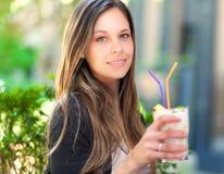 Belle femme ayant une boisson photo stock
