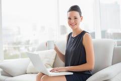 Belle femme bien habillée à l'aide de l'ordinateur portable tout en ayant le café sur le sofa photo stock