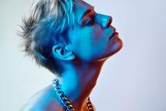 Belle femme blanche avec les cheveux courts de couleur et la lumière bleue images stock