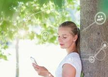 Belle femme blonde à l'aide du smartphone dans le parc image stock