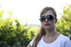 Belle femme blonde avec des lunettes de soleil en parc Photo libre de droits