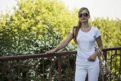 Belle femme blonde avec des lunettes de soleil en parc Image stock