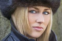 Belle femme blonde avec des yeux bleus dans le chapeau de fourrure Images stock