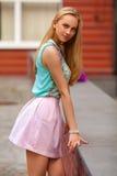 Belle femme blonde avec la pose rose de jupe extérieure Fille de mode photographie stock libre de droits